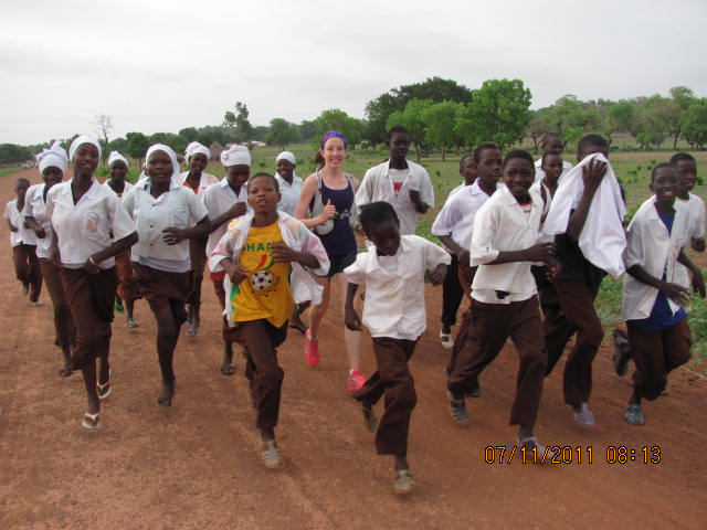 A Canadian nurse running with Gambian teenagers in Africa