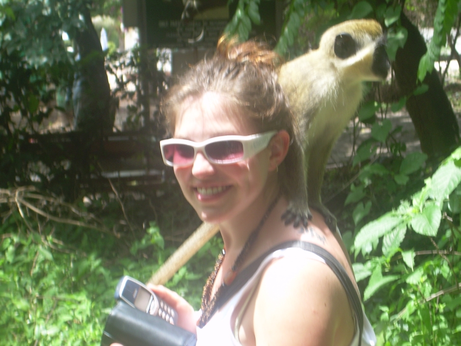 a monkey jumps on a canadian girl's back in Gambia