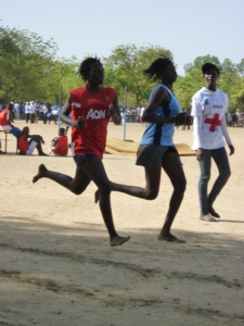 3 teenagers run on a sand track in The Gambia