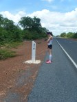 A runner and kilometer markers on the South Bank Road, The Gambia