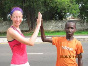 A Canadian runner high fives a young Gambian runner in Africa