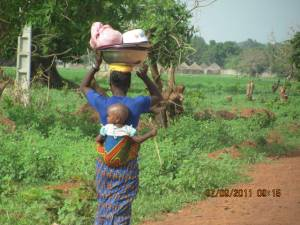 a mother carries a child on her back and wood on her head in Africa